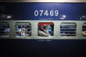 A passenger looks out of a carriage window as the passenger opposite him lies on his seat on the Abohar-Jodhpur passenger train also known by the locals as the Cancer Express in Bhatinda, Punjab. [Prashanth Vishwanathan (Bloomberg)]