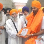 Baba Ajit Singh presenting directory to Bhai TIrlochan Singh son of Shaheed Bhai Amrik Singh